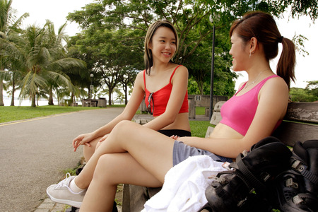 hair roller: Two women sitting side by side on park bench LANG_EVOIMAGES