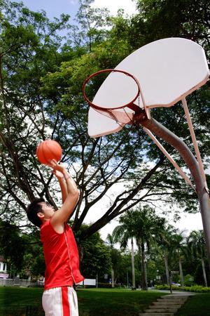 hombre disparando: Hombre que tira de baloncesto por un aro