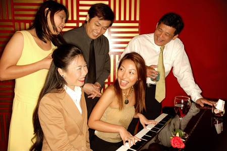 Woman playing the piano, friends around her