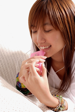 southeast asian ethnicity: Young woman listening to personal stereo