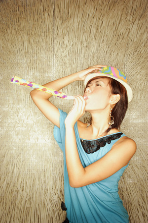 southeast asian ethnicity: Young woman wearing hat, blowing noisemaker LANG_EVOIMAGES