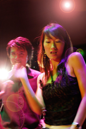 southeast asian ethnicity: Young man and woman at night club, dancing LANG_EVOIMAGES
