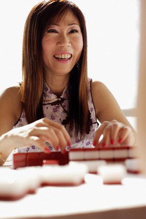 southeast asian ethnicity: Woman playing mahjong, smiling LANG_EVOIMAGES