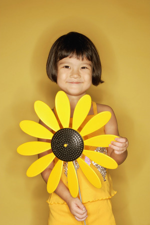3 4 years: Young girl standing holding plastic sunflower.