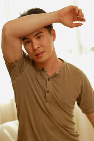Man raising arm, looking at camera
