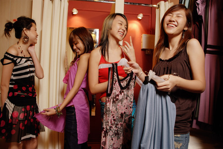 Four young women at shop, looking at and trying on clothes 版權商用圖片