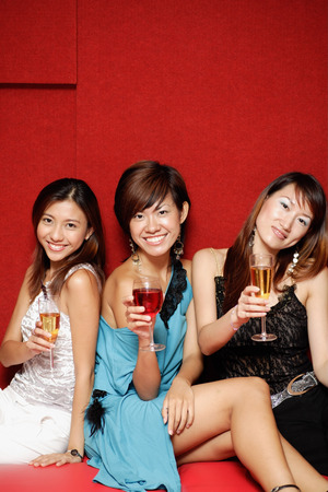 Young women, holding drinks and smiling at camera