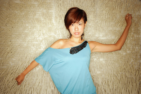 southeast asian ethnicity: Young woman standing, arms outstretched, looking at camera