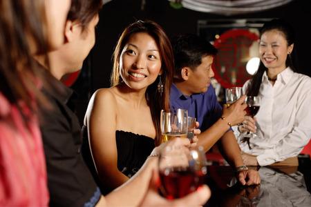 Men and women at bar, drinking Stock Photo