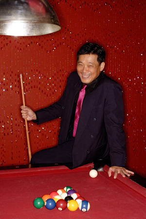 Man with pool cue leaning on table. Archivio Fotografico