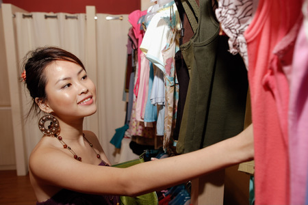 southeast asian ethnicity: Young woman looking through clothes rack