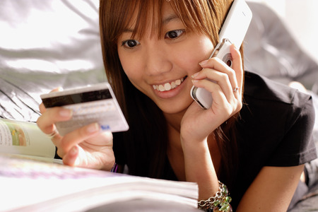 Young woman looking credit card, using phone Stock Photo