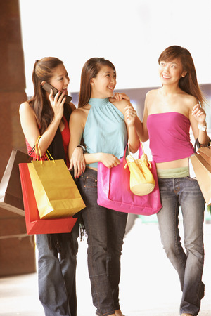Young women with shopping bags, walking side by side, one on the phone