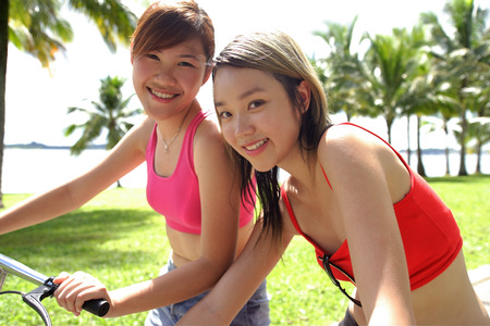 long weekend: Two women on bicycles, looking at camera