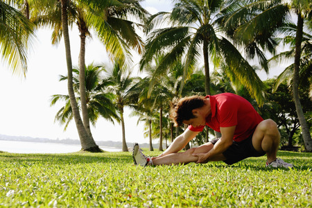Man doing stretching exercises in park, leg outstretched LANG_EVOIMAGES