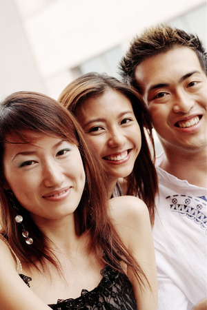 southeast asian ethnicity: Two young women and one young man, looking at camera, smiling LANG_EVOIMAGES
