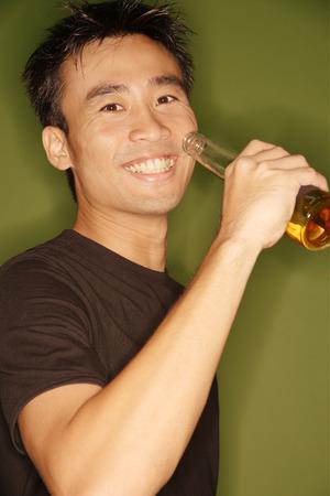 Young man raising beer bottle