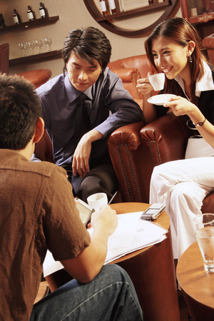 Young executives having a meeting in a cafe, woman drinking coffee Stock fotó