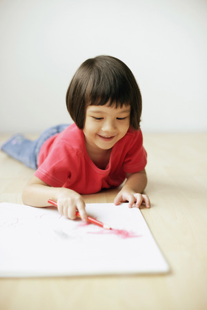 3 4 years: Young girl drawing on drawing pad, lying on front