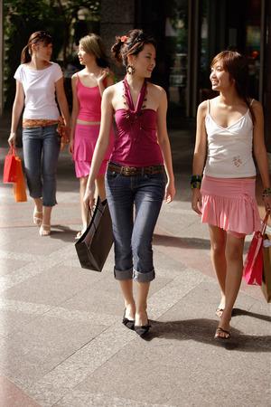 Young women walking and carrying shopping bags 免版税图像