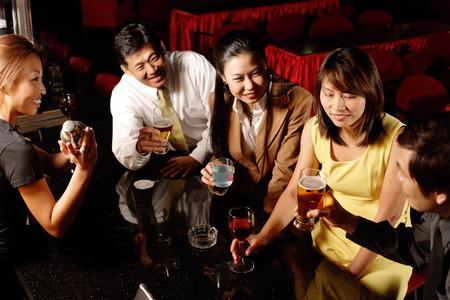 cocktail mixer: Couples drinking at bar, bartender shaking cocktail mixer