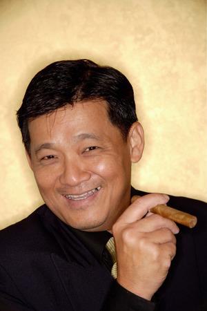 Man with cigar looking at camera, smiling