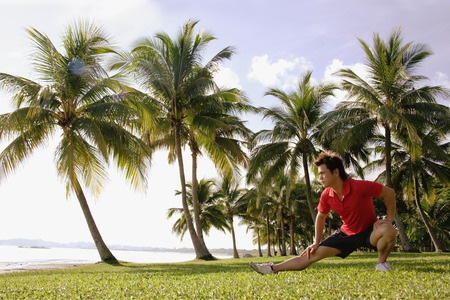 Man doing stretching exercises in park, hand on knee