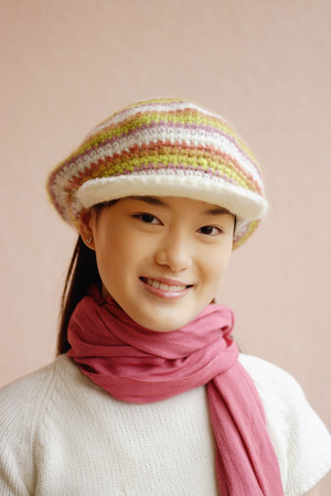 Young woman wearing cap, smiling, portrait
