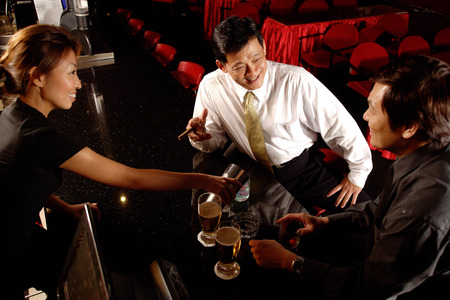 cocktail mixer: Two men at bar counter, bartender pouring drinks