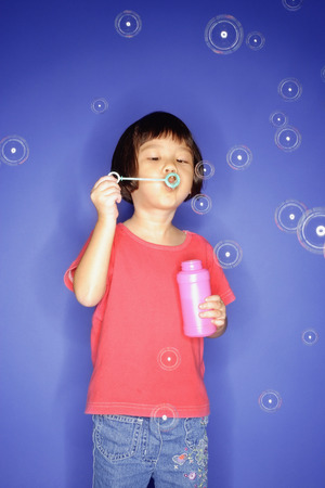 3 4 years: Young girl blowing bubbles, blue background LANG_EVOIMAGES