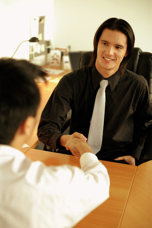 Two executives shaking hands across desk
