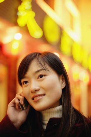 look pleased: Young woman using mobile phone, neon signs behind her