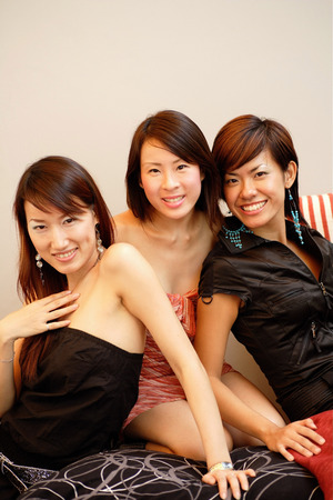 tube top: Three young women, sitting side by side, looking at camera