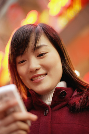 look pleased: Young woman with mobile phone, looking down