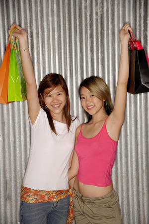 southeast asian ethnicity: Young women holding shopping bags looking at camera