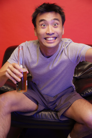 eyes wide open: Young man with beer bottle, eyes wide open