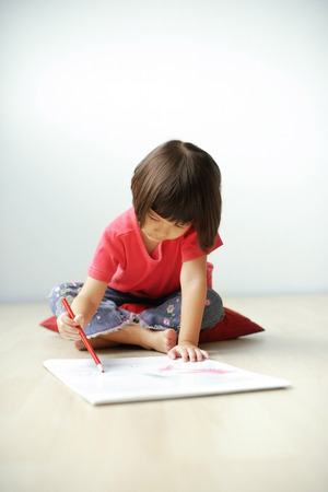 Young girl drawing on drawing pad. 免版税图像