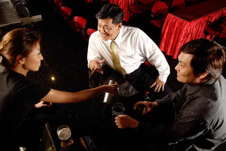 pass away: Two men at bar counter, bartender serving them