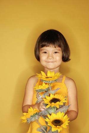 3 4 years: Young girl standing against yellow background, holding flowers, smiling