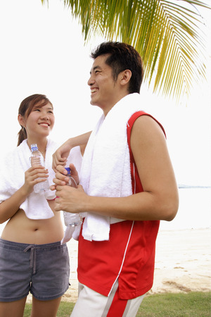 Couple standing at beach, side by side, holding water bottles