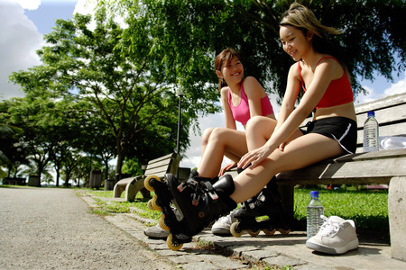 southeast asian ethnicity: Two women sitting side by side on park bench wearing roller blades