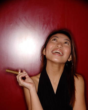 southeast asian ethnicity: Woman with cigar, looking up. LANG_EVOIMAGES