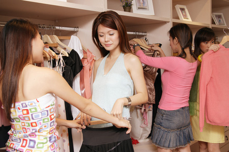 Young women looking through clothes rack at shop