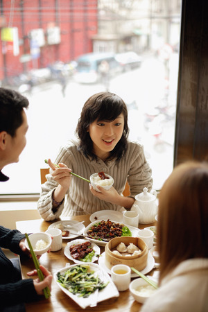Young woman and friends at a Chinese restaurant LANG_EVOIMAGES