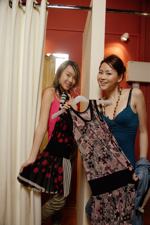 trying: Two women trying on clothes at shop, looking at camera