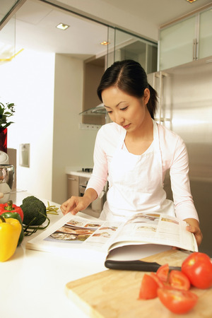 Young woman standing at kitchen counter, looking at cookbook