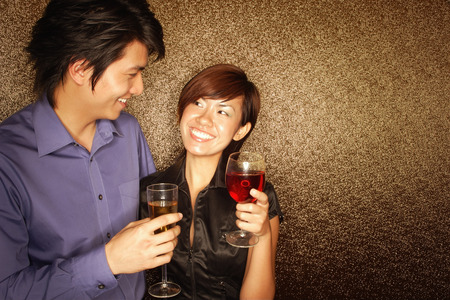 southeast asian ethnicity: Couple holding drinks, looking at each other