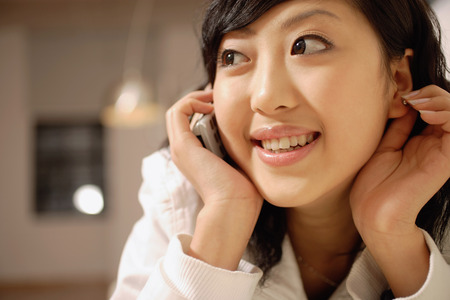 Young woman using mobile phone, touching ear and looking away LANG_EVOIMAGES