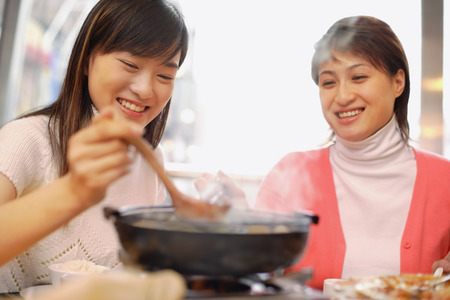 look pleased: Young women having soup at restaurant