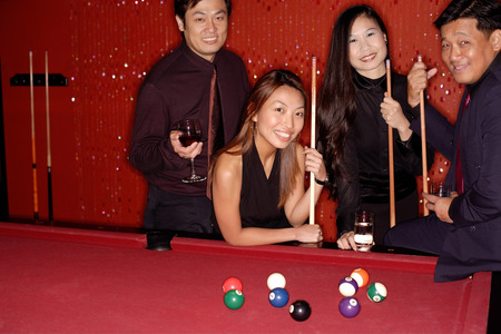 Men and women standing around pool table, looking at camera Archivio Fotografico
